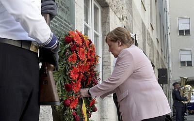 German Chancellor Angela Merkel adjusts a wreath during a memorial event at the Defence Ministry in Berlin, Germany, Saturday, July 20, 2019. On July 20, 2019 Germany marks the 75th anniversary of the failed attempt to kill Hitler in 1944. (AP Photo/Michael Sohn)