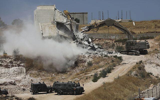 Israeli forces destroy a building in a Palestinian village of Sur Baher, east Jerusalem, Monday, July 22, 2019. . (AP Photo/Mahmoud Illean)