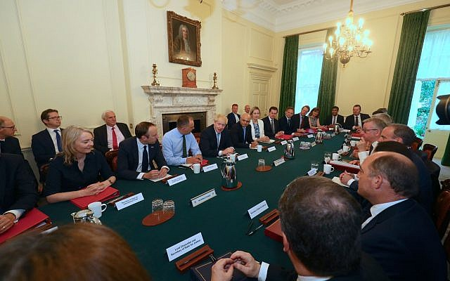 (from left, seated at table) International Trade Secretary Liz Truss, Health and Social Care Secretary Matt Hancock, Cabinet Secretary Sir Mark Sedwill, Prime Minister Boris Johnson, Chancellor of the Exchequer Sajid Javid, Works and Pensions Secretary and Minister for Women Amber Rudd,  Housing, Communities and Local Government Secretary Robert Jenrick, Transport Secretary Grant Shapps, Scottish Secretary Alister Jack, Culture Scretary Nicky Morgan, Chief Secretary to the Treasury Rishi Sunak, and Chief Whip Mark Spencer, as Prime Minister Boris Johnson holds his first Cabinet meeting at Downing Street in London. (Photo credit: Aaron Chown/PA Wire)