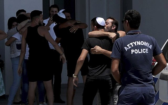 An Israeli teenager is embraced by relatives after being released from Famagusta police headquarters in southeast town of Paralimni, Cyprus, Sunday, July 28, 2019. A lawyer says Cyprus police will release all seven Israeli teenagers who were being detained as suspects in the alleged rape of a 19-year-old British woman. Cypriot Lawyer Yiannis Habaris, who represents two of the seven Israelis, told The Associated Press on Sunday the British woman has been arrested and faces a public nuisance charge. (AP Photo/Petros Karadjias)