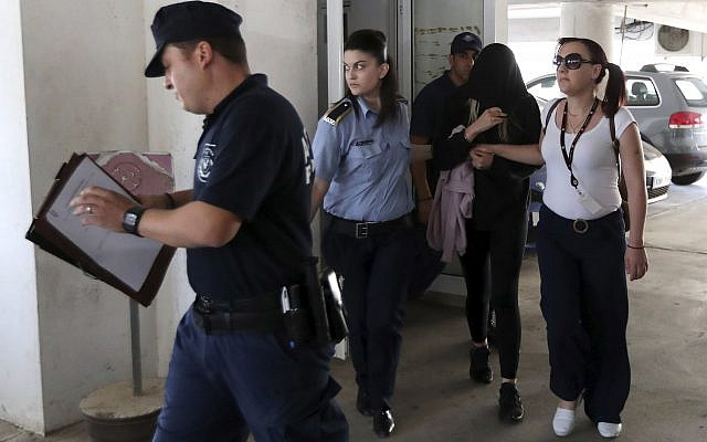 Police officers escort a 19-year-old British woman, second from right, out of Famagusta court in town of Paralimni, Cyprus, Monday, July 29, 2019. . (AP Photo/Petros Karadjias)