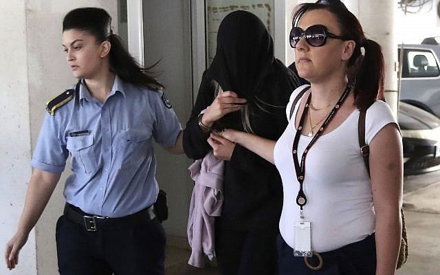 Police officers escort a 19-year-old British woman, center, from the Famagusta court in town of Paralimni, Cyprus, Monday, July 29, 2019. (AP Photo/Petros Karadjias)