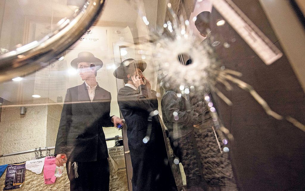 A bullet hole in a glass door of a synagogue that was the scene of a terror attack. Two Palestinians armed with a cleaver and a gun burst in to a shul in the Jerusalem neighbourhood of Har-Nof, killing four Israeli men and wounding several others