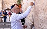 Sajid Javid places a note into the wall at the Kotel