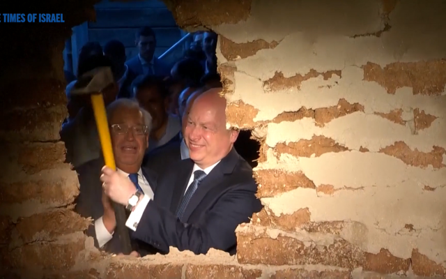 Jason Greenblatt and David Friedman use a sledge hammer to break the wall during the ceremony (screenshot)