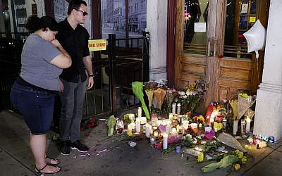 Mourners visit a makeshift memorial outside Ned Peppers bar following a vigil at the scene of a mass shooting, Sunday, Aug. 4, 2019, in Dayton, Ohio. A masked gunman in body armor opened fire early Sunday in the popular entertainment district in Dayton, killing several people, including his sister, and wounding dozens before he was quickly slain by police, officials said. (AP Photo/John Minchillo)