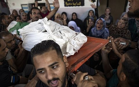 Mourners carry the body of Palestinian Hamas militant, Mohammad Abu Namous, 27, out of the family home during his funeral in the Jabaliya refugee camp, northern Gaza Strip, Sunday, Aug. 18, 2019. (AP Photo/Khalil Hamra)