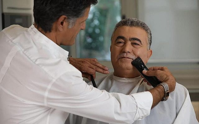 Amir Peretz having his moustache shaved off (Source: https://www.facebook.com/Peretz.Amir/)