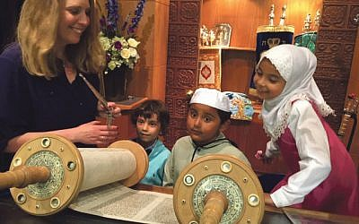 Rabbi Miriam Berger shows young members of the Somali Bravanese community a Torah