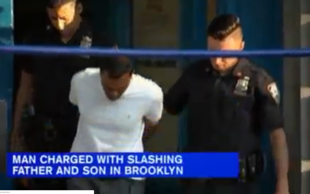 Screenshot from WABC-TVvideo shows a suspect being led away by police in handcuffs