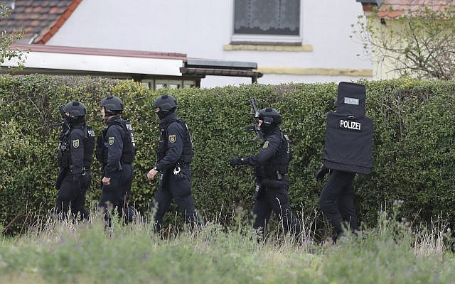 Police officers secure the surrounding of Landsberg, Germany, Wednesday, Oct. 9, 2019. One or more gunmen fired several shots on Wednesday in the German city of Halle. Police say a person has been arrested after a shooting that left two people dead. (Jan Woitas/dpa via AP)