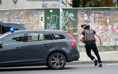 Police officer runs on a road in Halle, Germany, Wednesday, Oct. 9, 2019. (Sebastian Willnow/dpa via AP)