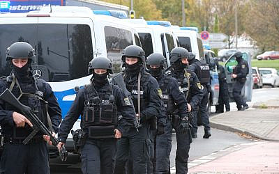 Police officers walk on a road in Halle, Germany, Wednesday, Oct. 9, 2019. One or more gunmen fired several shots on Wednesday in the German city of Halle. Police say a person has been arrested after a shooting that left two people dead. (Sebastian Willnow/dpa via AP)