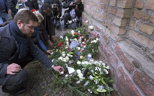 People place down flowers in front of a synagogue in Halle, Germany, Thursday, Oct. 10, 2019  (AP Photo/Jens Meyer)
