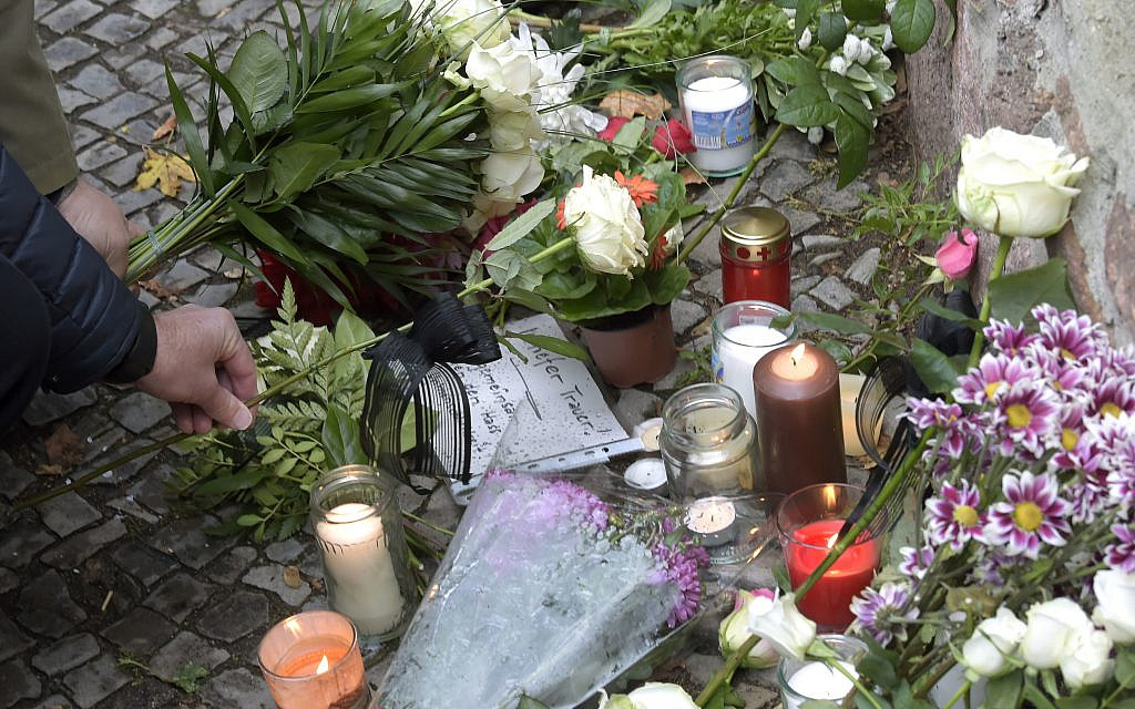 People place down flowers in front of a synagogue in Halle, Germany, Thursday, Oct. 10, 2019. A heavily armed assailant ranting about Jews tried to force his way into a synagogue in Germany on Yom Kippur, Judaism's holiest day, then shot two people to death nearby in an attack Wednesday that was livestreamed on a popular gaming site. (AP Photo/Jens Meyer)