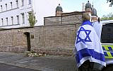 A person with a flag of Israel stands next to flowers and candles in front of a synagogue in Halle, Germany, following a terror shooting on Yom Kippur (AP Photo/Jens Meyer via Jewish News)