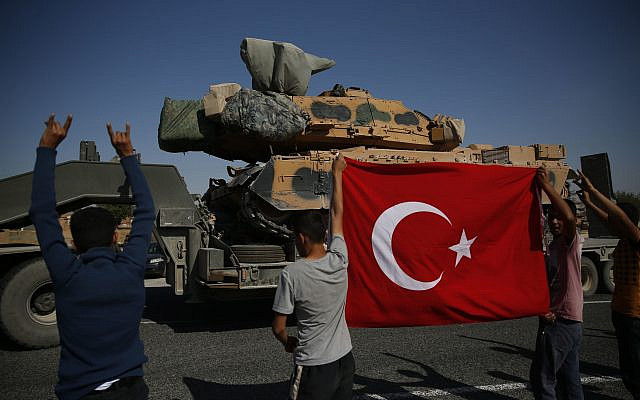 Local residents applaud as a convoy of Turkish forces trucks transporting tanks is driven in Sanliurfa province, southeastern Turkey, at the border with Syria, Saturday, Oct. 12, 2019.  (AP Photo/Lefteris Pitarakis)