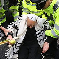 Rabbi Jeffrey Newman is arrested as protesters continue to block the road outside Mansion House in the City of London, during an XR climate change protest. Rabbi. Photo credit: Gareth Fuller/PA Wire