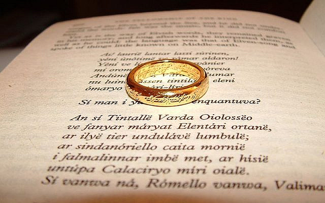 A page of the book The Lord of the Rings, along with a replica of the Unique Ring in the middle. (Wikipedia/ Zanastardust https://www.flickr.com/photos/zanastardust/146652127/)