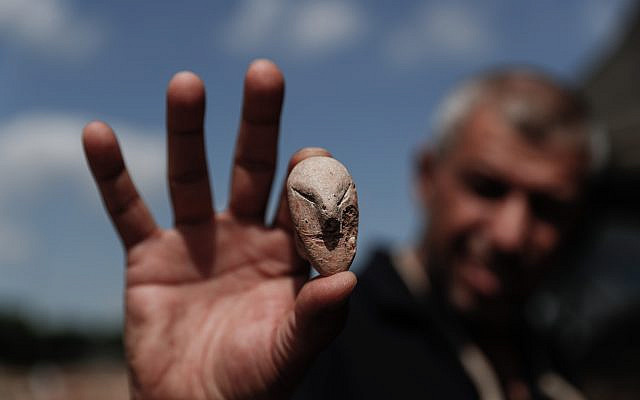 A picture taken on October 06, 2019 shows a figurine of a human face unearthed at the archaeological site of En Esur (Ein Asawir) where a 5000-year-old city was uncovered, near the Israeli town of Harish on October 06, 2019. Photo by: JINIPIX