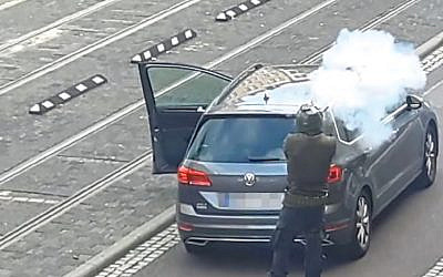 The suspect fires his weapon from behind his car
