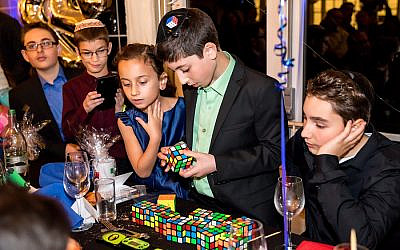 Pictured 13 year-old Rafi Niman, from Borehamwood, solved 13 Rubik's cube in under four minutes at his bar mitzvah