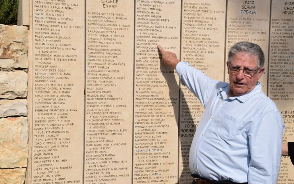 Yossi Mor pointing to Melpomeni Dina's name, inscribed on the Wall of Honor in the Garden of the Righteous Among the Nations at Yad Vashem  (Credit: Yad Vashem)
