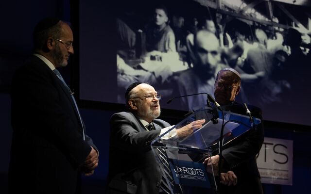 Holocaust Survivor Josef Lewkowicz stood next to a photograph of himself in Ebensee camp, with Tzvi Sperber and Rabbi Naftali Schiff  (Credit: Blake Ezra Photography)