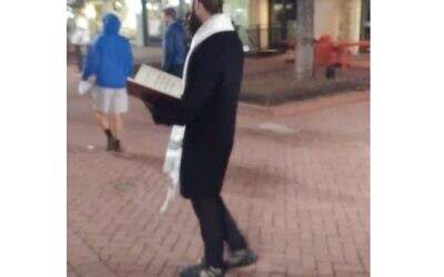 Screenshot from Twitter, showing a man dressed as a Jew, handing out Holocaust denial leaflets
