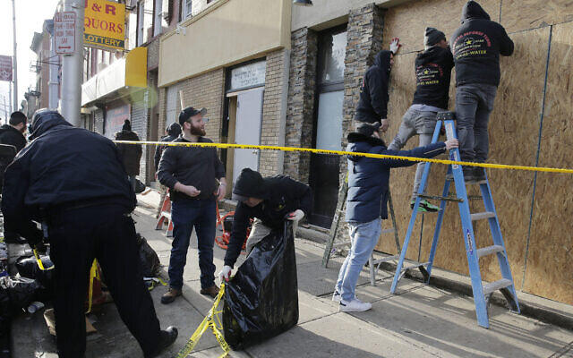 People board up the front of a kosher supermarket thats was the site of a gun battle in Jersey City, N.J., Wednesday, Dec. 11, 2019. The two gunmen in a furious firefight that left multiple people dead in Jersey City clearly targeted the Jewish market, the mayor said Wednesday, amid growing suspicions the bloodshed was an anti-Semitic attack. (AP Photo/Seth Wenig)