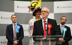 Labour leader Jeremy Corbyn speaks after winning his seat in the election - but witnessing his party suffering heavy losses. On the right is Jewish Brexit Party candidate, Yosef David. (Photo credit: Joe Giddens/PA Wire)