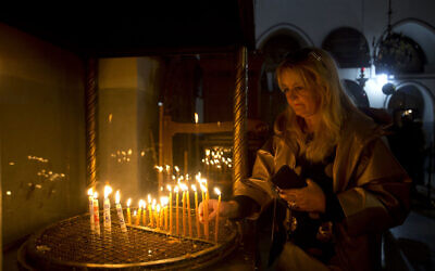 A visitor lights a candle at the Church of the Nativity built on top of the site where Christians believe Jesus Christ was born on Christmas Eve, in the West Bank City of Bethlehem, Tuesday, Dec. 24, 2019. (AP Photo/Majdi Mohammed)