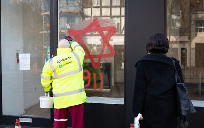 A council cleaner removes anti-semitic graffiti in the form of numbers, 9 11, and a Star of David, on a shop window in Belsize Park, North London. ( Photo credit: Aaron Chown/PA Wire_