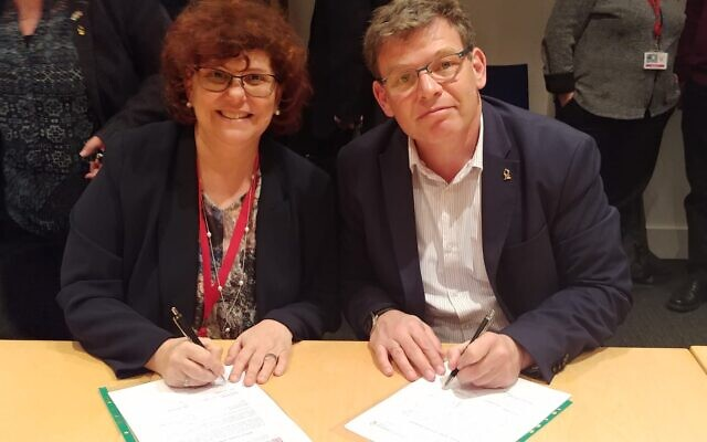 BGU Rector Prof. Chaim Hames (right) and Prof. Dimitra Simeonidou of the University of Bristol sign the MOU on Monday. (Photo Credit: Daphna Frucht/British Embassy Israel)