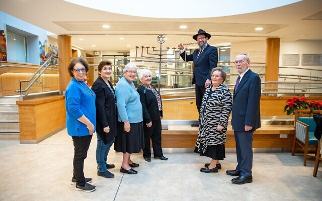 Left to right: Stephanie Lewis, Judith Goodman,  Jeanette, Linda, Mel Zeffert and his spouse, Rabbi Menachem Junik with the new menorah at Jewish Care's Betty and Asher Loftus Centre (Credit: Jewish Care)