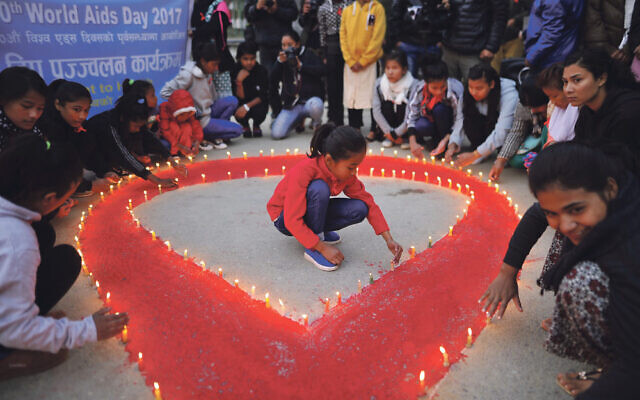 People light candles around the symbol for last week's World Aids Day