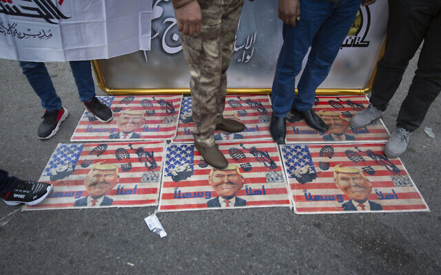 Mourners step over a U.S. flags with pictures of President Trump while waiting for the funeral of Iran's top general Qassem Soleimani and Abu Mahdi al-Muhandis, deputy commander of Iran-backed militias in Iraq known as the Popular Mobilization Forces, in Baghdad, Iraq, Saturday, Jan. 4, 2020. (AP Photo/Nasser Nasser)