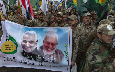 """Iraqi militiamen march and chant anti U.S. slogans while carrying a picture of Soleimani, left and al-Muhandis, with Arabic that reads """"our Martyr leaders,"""" during the funeral of Iran's top general Qassem Soleimani and Abu Mahdi al-Muhandis, deputy commander of Iran-backed militias in Iraq known as the Popular Mobilization Forces, in Baghdad, Iraq, Saturday, Jan. 4, 2020. Thousands of mourners chanting """"America is the Great Satan"""" marched in a funeral procession Saturday through Baghdad for Iran's top general and Iraqi militant leaders, who were killed in a U.S. airstrike. (AP Photo/Nasser Nasser)"""