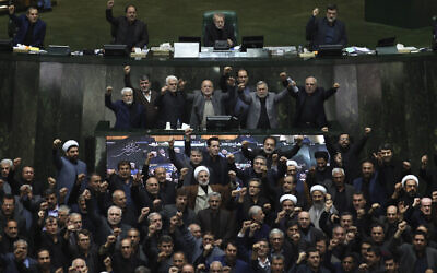 Iranian lawmakers chant anti-American and anti-Israeli slogans to protest against the U.S. killing of Iranian top general Qassem Soleimani, at the start of an open session of parliament in Tehran, Iran, Sunday, Jan. 5, 2020.  (Mohammad Hassanzadeh/Tasnim News Agency via AP)