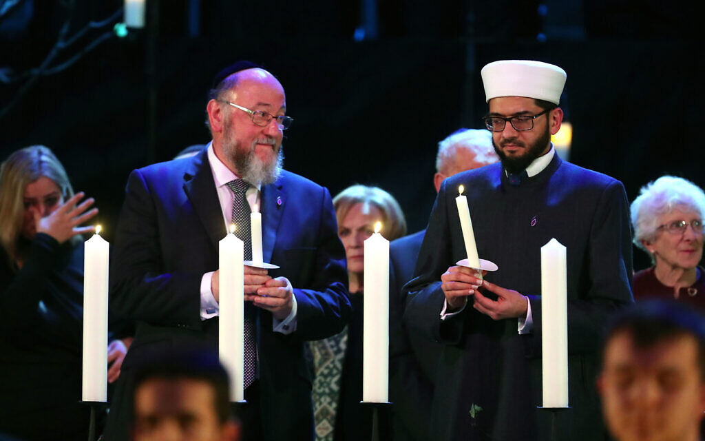Chief Rabbi Ephraim Mirivis (left) lights a candle during the UK Holocaust Memorial Day Commemorative Ceremony at Central Hall in Westminster, London.  (Photo credit: Chris Jackson/PA Wire)