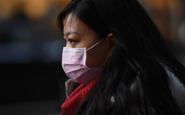 A woman wears a face mask while walking down Kingsway in Holborn, London. PA Photo.: Victoria Jones/PA Wire