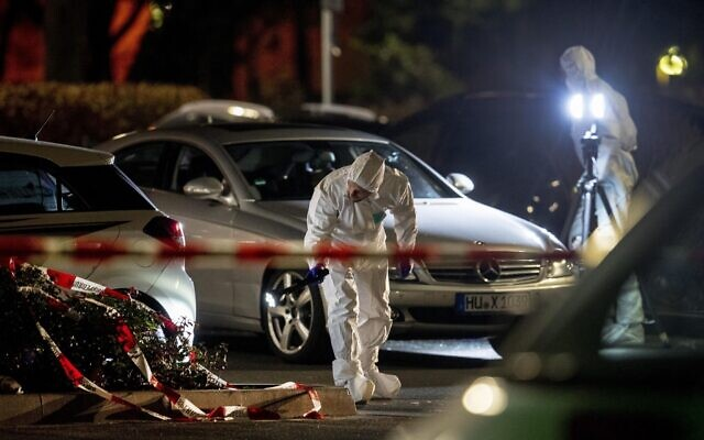 Forensics investigate at the scene after a shooting in central Hanau, Germany Thursday, Feb. 20, 2020. Eight people were killed in shootings in the German city of Hanau on Wednesday evening, authorities said.  (AP Photo/Michael Probst)
