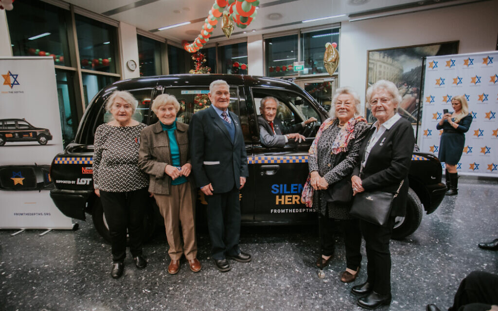 Group of Righteous Among The Nations in front of the Silent Hero taxi being driven by Holocaust Survivor Edward Mosberg (Credit: From the Depths/ Jonny Daniels)