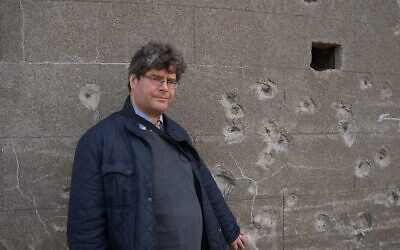Marcus Roberts standing next to a wall on Alderney believed to be an execution site.