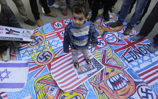 A Palestinian child stands on the illustrations of the British Union flag, the Israeli flag, and an American flag during a protest against the American peace plan in the Middle East, in Gaza City. (Photo by Mahmoud Issa / SOPA Images/Sipa USA)
