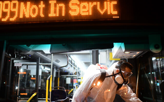 Workers wearing protective suits disinfect a bus as a preventive measure amid fears over the spread of the coronavirus, in Tel Aviv - as public transport is shut down. Photo by: Tomer Neuberg-JINIPIX