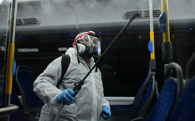 Workers wearing protective suits disinfect a bus as a preventive measure amid fears over the spread of the coronavirus, in Tel Aviv  Photo by: Tomer Neuberg-JINIPIX