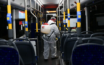 Workers wearing protective suits disinfect a bus as a preventive measure amid fears over the spread of the coronavirus, in Tel Aviv.  Photo by: Tomer Neuberg-JINIPIX