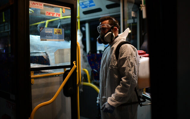 Workers wearing protective suits disinfect a bus as a preventive measure amid fears over the spread of the coronavirus, in Tel Aviv on March 9, 2020,  (Photo by: Tomer Neuberg-JINIPIX)
