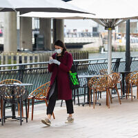 A woman wearing a protective face mask and gloves walks past empty table outside a bar, at Canary Wharf, London, as commuters switch to working from home and the public are urged to avoid social contact to prevent the spread of coronavirus. (Photo credit: Dominic Lipinski/PA Wire)